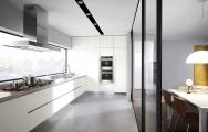 Moderná biela kuchyňa s zafrézovanými úchytkami spolu s obývačkou